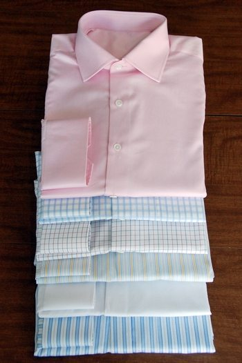Stack of custom dress shirts of different colors and patterns